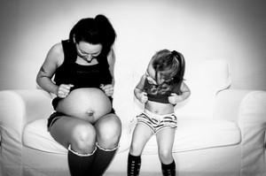 une petite fille compare son ventre à celui de sa maman enceinte